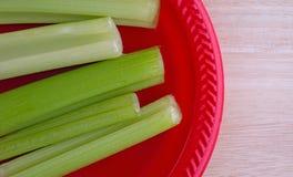 Palillos de apio en una opinión superior de la placa roja Imagen de archivo