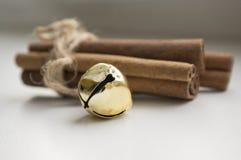 Palillos de canela crudos frescos en la tabla de madera atada con guita y cascabeles naturales imagenes de archivo