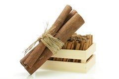 Palillos de canela envueltos juntos y un cajón de madera Imagenes de archivo