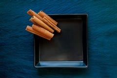 Palillos de canela secados pila colocados en la placa negra que colocó en fondo de la superficie de la piedra azul fotos de archivo