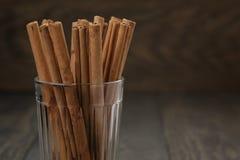 Palillos de canela verdaderos en vidrio en la tabla de madera Fotografía de archivo