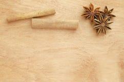 Palillos de canela y anís de estrella en una tabla de madera imagenes de archivo