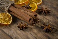 Palillos de canela y estrellas del anís en la tabla de madera Imagen de archivo
