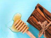 Palillos de canela y miel derramada en azul Foto de archivo