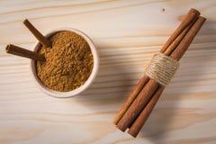 Palillos de cinamomo en tazón de fuente de madera Imagen de archivo