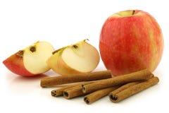 Palillos de cinamomo secados y una manzana fresca Foto de archivo libre de regalías