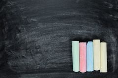 Palillos de la tiza coloreada en una pizarra Fotos de archivo