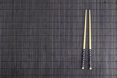 Palillos de madera en la estera de bambú marrón de la paja Fotografía de archivo libre de regalías