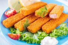 Palillos de pescados fritos Filetes de pescados Palillos de pescados con el limón y las salsas preparados foto de archivo