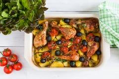 Palillos de pollo cocidos en plato rojo Cocinado con los tomates de cereza, las aceitunas negras, el romero y las patatas fotos de archivo libres de regalías