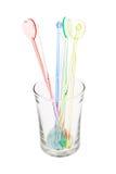 Palillos de swizzle plásticos coloridos en vidrio Foto de archivo