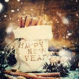 Palillos del canela en un bolso de lino bordado con Feliz Año Nuevo Nieve exhausta Imágenes de archivo libres de regalías