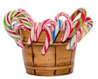Palillos del caramelo y piruletas coloreados en un florero marrón, fondo aislado, blanco de la Navidad Foto de archivo libre de regalías