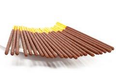 Palillos del chocolate en un dulce japonés del platillo. Aún-vida en un fondo blanco Fotos de archivo libres de regalías