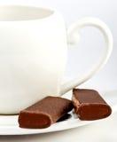 Palillos del chocolate en un platillo. Aún-vida en un fondo blanco Fotografía de archivo libre de regalías