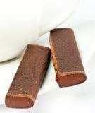 Palillos del chocolate en un platillo. Aún-vida en un fondo blanco Fotos de archivo libres de regalías