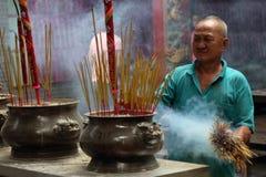 Palillos del incienso del hombre que llevan en templo budista Imagenes de archivo