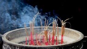 Palillos del incienso que queman en pote gigante delante del templo budista metrajes