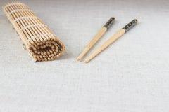 Palillos del sushi con la estera de bambú rodada de la paja Imagenes de archivo