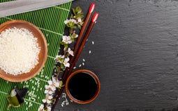 Palillos del sushi, cuenco de la salsa de soja, arroz y bloss japoneses de Sakura Fotos de archivo