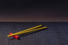 Palillos del sushi en la estera de la paja del bambú negro Foto de archivo