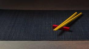 Palillos del sushi en la estera de la paja del bambú negro Imagenes de archivo