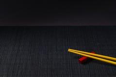 Palillos del sushi en la estera de la paja del bambú negro Fotos de archivo
