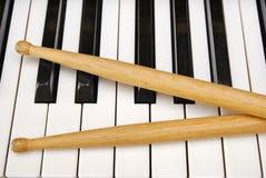 Palillos del tambor en el teclado de piano Foto de archivo libre de regalías