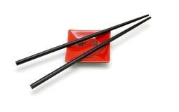Palillos en el pequeño platillo del cuadrado rojo Imagen de archivo