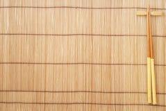 Palillos en fondo de bambú marrón de la estera Fotos de archivo