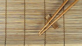 Palillos en la estera de bambú Fotografía de archivo