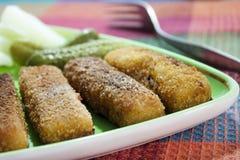 Palillos fritos de la merluza con los pepinos Fotografía de archivo