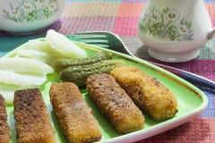 Palillos fritos de la merluza con los pepinos Imágenes de archivo libres de regalías