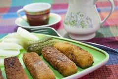 Palillos fritos de la merluza con los pepinos Foto de archivo