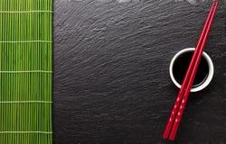 Palillos japoneses del sushi sobre el cuenco de la salsa de soja Fotos de archivo libres de regalías