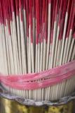 Palillos rojos del incienso en urna decorativa Fotografía de archivo