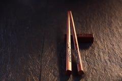 Palillos tallados de la tajada en la tabla de madera en luz caliente Fotografía de archivo libre de regalías