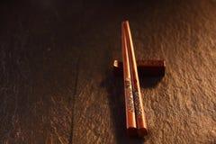 Palillos tallados de la tajada en la tabla de madera en luz caliente Imágenes de archivo libres de regalías