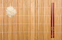 Palillos y arroz sobre una estera de lugar Imagenes de archivo