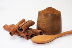 Palillos y canela en polvo de canela en las placas y la cuchara de madera Fotos de archivo