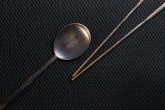 Palillos y cuchara en escena oscura Fotos de archivo libres de regalías