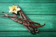 Palillos y flor de la vainilla en fondo imagenes de archivo
