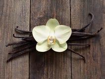 Palillos y flor de la vainilla en la madera Fotografía de archivo