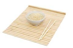 Palillos y tazón de fuente en la estera de bambú imagen de archivo