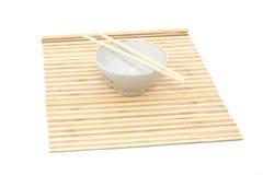 Palillos y tazón de fuente en la estera de bambú imágenes de archivo libres de regalías