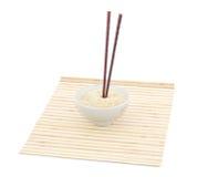 Palillos y tazón de fuente en la estera de bambú fotografía de archivo libre de regalías