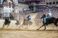 Palio di Siena. SIENA, ITALY - AUGUST 16, 2015 : Riders compete in the horse race Palio di Siena in the medieval square Piazza del Campo in Siena, Italy royalty free stock photo