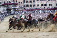 Palio di Siena. SIENA, ITALY - AUGUST 16, 2015 : Riders compete in the horse race Palio di Siena in the medieval square Piazza del Campo in Siena, Italy stock image