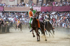 Palio di Siena. SIENA, ITALY - AUGUST 16, 2015 : Riders compete in the horse race Palio di Siena in the medieval square Piazza del Campo in Siena, Italy royalty free stock photography