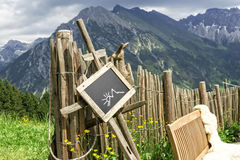 Palisade chalkboard mountains. Wooden palisade with chalkboard hint panel and lambskin coated bench in front of a mountain landscape. Chalkboard with empty space Stock Image